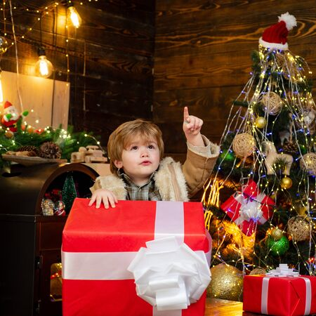 Happy child with Christmas gift. Happy kid having fun with big gift box. Christmas decorations. Wish you merry Christmas.