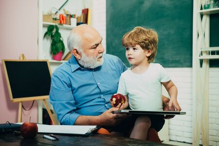 Funny little child having fun on blackboard background. Happy cute Grandson and Grandfather sitting at a desk indoors. Father and son. Old and Young. Concept of a retirement age.