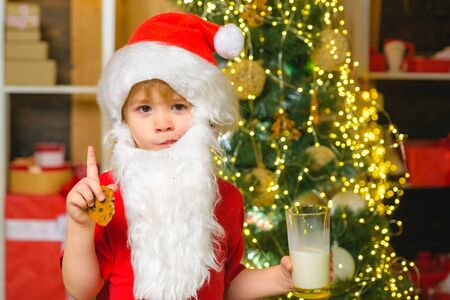 Santa boy in Santa hat. Funny child Christmas. Santa Claus - bearded funny child. Happy Santa Claus - little child boy with glass of milk and cookie. Christmas food and drink.