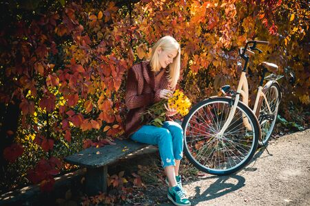 Dreamy girl with blonde hair in knit sweater. Beautiful young brunette sitting on a fallen autumn leaves in a park. Autumn Clothing and color trends. 写真素材