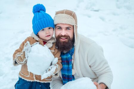 Christmas Celebration holiday. Father and son play in winter clothes. Happy father and son play on winter Christmas time. Father and son making snowball on winter white background.