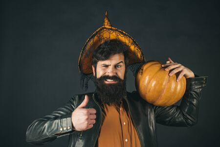 Halloween Man posing with pumpkins. Scary hipster man with beard in Halloween hat. Halloween man with pumpkin - Holidays celebration concept. Happy Halloween Weekends. Standard-Bild