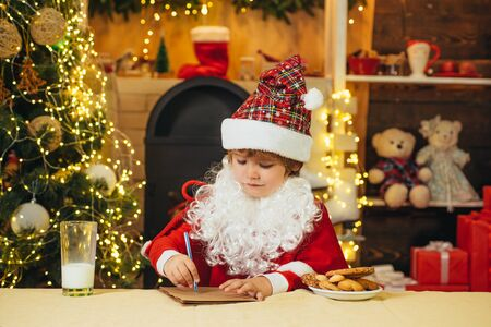 Santa kid writes the letter to children. Little Santa reads the letter to children. Little Santa picking cookie and glass of milk at home. Stock Photo