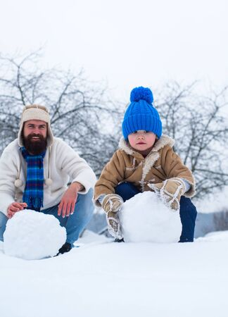 Happy father and son making snowman in the snow. Handmade funny snow man. Best winter game for happy family.