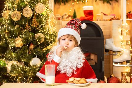 Santa Claus takes a cookie on Christmas Eve as a thank you gift for leaving presents. Portrait of surprised and funny Santa. Christmas food and drink. Stock Photo