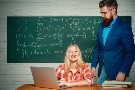 Teacher teaches a student. School day. Science and education concept. Teacher and student sit together at education class. Teachers day. Bearded tutor helping his student. Stock Photo