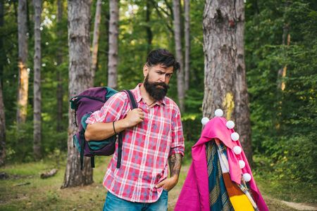 Happy man in summer. Camping tent on sunny day. Shelter of branches. Active people. Tourism rest on nature. Story in hovel.