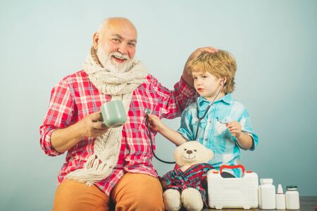 Smiling little boy playing doctor and listening old grandfather with stethoscope. Patient recovery is going well. Child boy stroking the head of the sick grandfather. Family doctor.