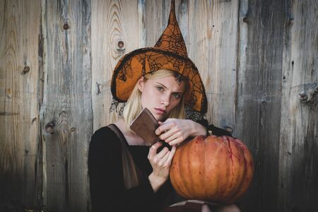 Halloween horror concept. Preparation Halloween holiday. Sensual woman in witch Halloween costume with jack o lantern. Halloween art design. Jack-o-lantern. Stock fotó
