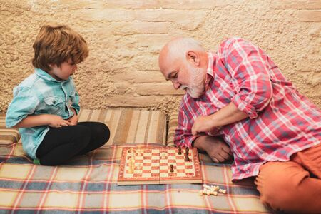 Generations. Senior man teaching his grandson to play chess. Cute little boy playing chess. Chessman. Checkmate.