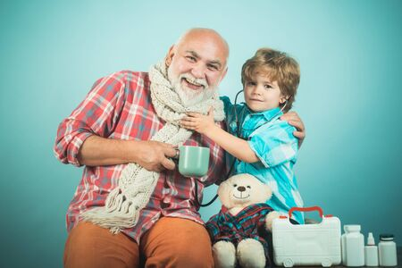 Sick grandfather in a warm scarf around his neck. Smiling kid doctor and old man patient on color background.