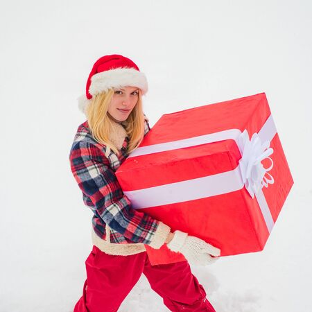Christmas Girl push big gift box full length concept. Winter holiday. Promotion and bonuses. Hipster Girl with Christmas gift on snow Winter landscape.