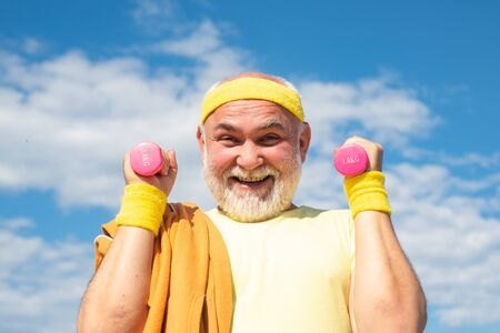 Happy Senior sportman exercising with lifting dumbbell on blue sky background. Isolated, copy space. Stockfoto