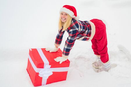 Woman in Santa Claus dress giving you big red gift over white snow background. Happy woman standing on white snow background and holding a giant red gift box with both hands.