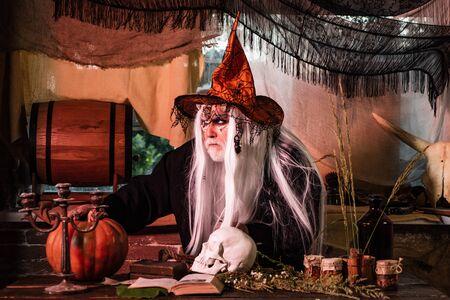 Halloween-Teufel mit blutigem professionellem Make-up. Halloween-Mann mit Blut-Make-up. Das verrückte Jokergesicht. Beängstigender Halloween-Mann mit Hut - Studioaufnahme Nahaufnahme.
