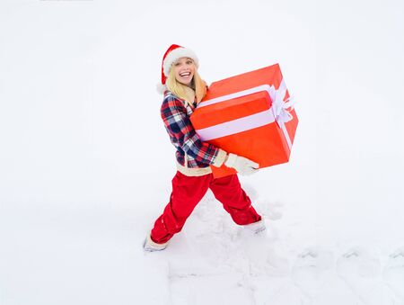 Woman carrying a big present isolated on snow winter background - full length. Funny woman holding a big Christmas present.