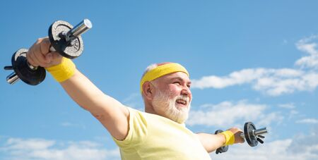 Senior man lifting dumbbell. Portrait of healthy happy smile senior. Senior sportsman in sport center. Senior man in his seventies training and lifting weigh. Like sports.