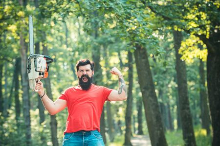 Woodworkers lumberjack. Lumberjack with chainsaw on forest background. Agriculture and forestry theme. Reklamní fotografie