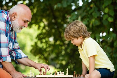 Old man with young child boy playing chess. Childhood. Grandfather and grandson concept. Chess piece. Cute boy developing chess strategy. Stockfoto