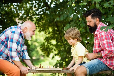 Elderly man practicing sports on blue sky background. Like chess game. Male Multi Generation Portrait. Senior man teaching his grandson to play chess.