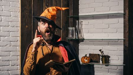 Scary face man with horror Make up holding Pumpkin head jack lantern on sky background. Evil witcher with red hair and beard in a black cloak reading a book of spells. Halloween, holidays celebration.