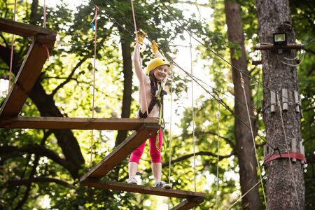 Happy Little girl climbing a tree. Go Ape Adventure. Hike and kids concept. Cute little girl in climbing safety equipment in a tree house or in a rope park climbs the rope. Stock Photo