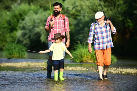 Man with his son and father on river fishing with fishing rods. Father teaching his son fishing against view of river and landscape. Men day.