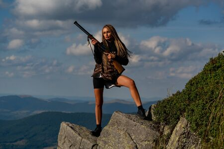 Hunter girl. Hunting in America. Young hunter woman holding gun and walking in forest. Woman with gun. Track down. Process of duck hunting. 版權商用圖片