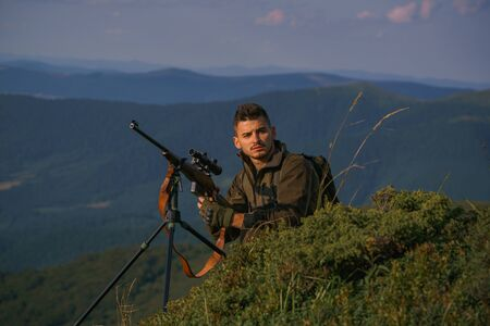 Hunter on Big game or small game. Hunter with Powerful Rifle with Scope Spotting Animals. Male with a gun. Man hunter with a gun.