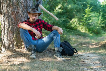 Handsome man lumberjack with a large ax examines the tree before felling. Deforestation is a major cause of land degradation and destabilization of natural ecosystems.