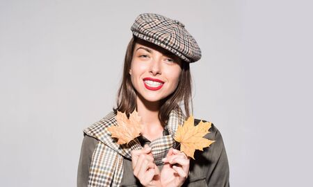 Surprise woman playing with leaves and looking at camera. Girl preparing for Autumn sale. Attractive young woman in a seasonal clothes. Fashion portrait of beautiful sensual woman in hat and scarf.