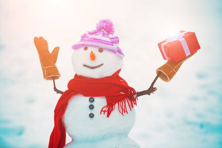 Snowman in a scarf and hat. Snowmen standing in winter Christmas landscape. Funny snowman in stylish hat and scarf on snowy field. Greeting snowman