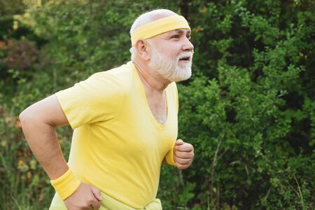 Senior man jogging in park. Like sports. Funny sporty old sportsman finished his work out. Old sport man running outside at park. Age is no excuse to slack on your health. Stock Photo