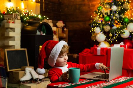 Buy christmas gifts online. Christmas shopping concept. Gifts service. Little genius. Santa little helper. Little boy santa hat and costume having fun. Boy child with laptop near christmas tree Stock Photo