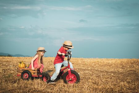 Little bikers with retro tricycle. Eco farm workers. Two little children on countryside farm. sweet childhood. Eco living. Childhood concept. Nature and children lifestyle. Summer leisure. Stock Photo