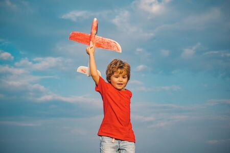 Boy with plane on meadow. Summer at countryside. Success and child leader concept. Childhood dream imagination concept. Kid pilot having fun on meadow. Active leisure with kids.