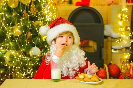 Santa boy child eating cookies and drinking milk. Santa Claus - bearded funny child. Santa in home. Santa Claus takes a cookie on Christmas Eve as a thank you gift for leaving presents.