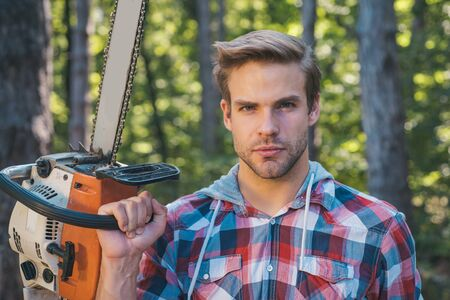Handsome young man with axe near forest - close up portrait. The Lumberjack working in a forest. Logging. Firewood as a renewable energy source. Woodcutter with chainsaw on sawmill.