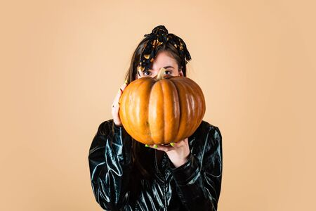 Beauty halloween witch with big eyes. Young Beautiful Woman with pumpkin. Beauty Woman face Portrait for halloween banner. Yellow background isolated. Stock Photo