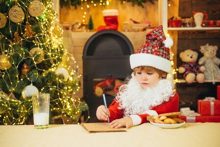 Santa Claus writes the letter. Santa reads the letter from children. Santa boy in Santa hat.