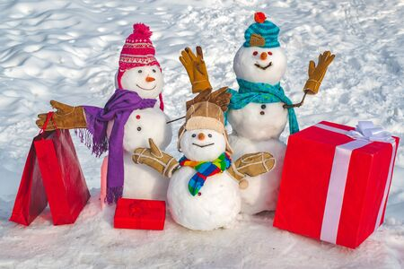 Happy snowman couple and snowman child with Christmas gift standing in winter Christmas landscape. New Year greeting card. Merry Christmas and happy new year greeting card.