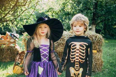 Halloween kids party in garden with pumpkins. jack-o-lantern. Happy Halloween Children girl and boy sit on hay or straw on meadow in autumn. Happy Halloween with sweets candles.