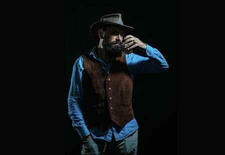 Man Bartender holding glass of whisky. Bearded handsome man holding glass of whiskey. Man with beard holds glass of brandy. Stock Photo
