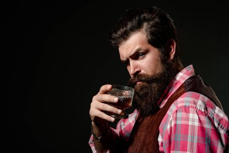 Bearded handsome man holding glass of whiskey. Sipping finest whiskey. Fashion style concept. Businessman gets rid of stress with whiskey.