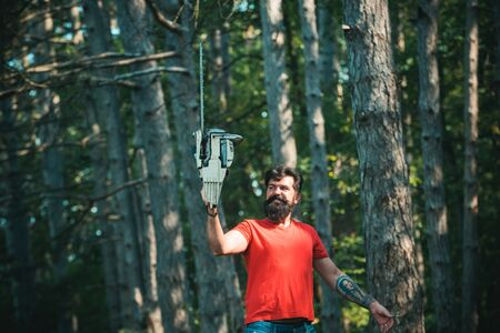 Logging. Deforestation is a major cause of land degradation and destabilization of natural ecosystems. Chainsaw. Lumberjack with chainsaw on forest background.