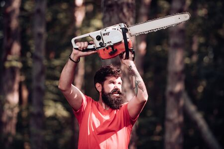 Stylish young man posing like lumberjack. Lumberjack on serious face carries chainsaw. Lumberjack worker standing in the forest with chainsaw. Man doing mans job.
