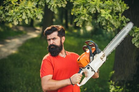 Professional lumberjack holding chainsaw in the forest. Lumberjack holding the chainsaw. Agriculture and forestry theme. Woodworkers lumberjack.