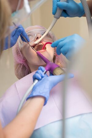 Dentist curing a woman patient in the dental office in a pleasant environment. Beautiful girl in dental chair on the examination at dentist.