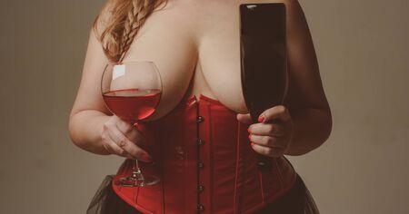 Gourmand et plaisir. Vin devant de gros seins. Le modèle taille plus tient un verre de vin. Fille montre ses seins magnifiques. Verre à vin femme et bouteille. Grande taille. Sommelier femme plantureuse brutale Banque d'images