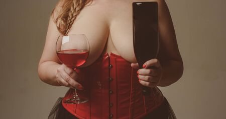 Gourmet and pleasure. Wine in front of big breasts. Plus size model hold glass of wine. Girl shows her gorgeous breasts. Woman wine glass and bottle. Big boobs size. Brutal busty woman sommelier Archivio Fotografico - 130260819